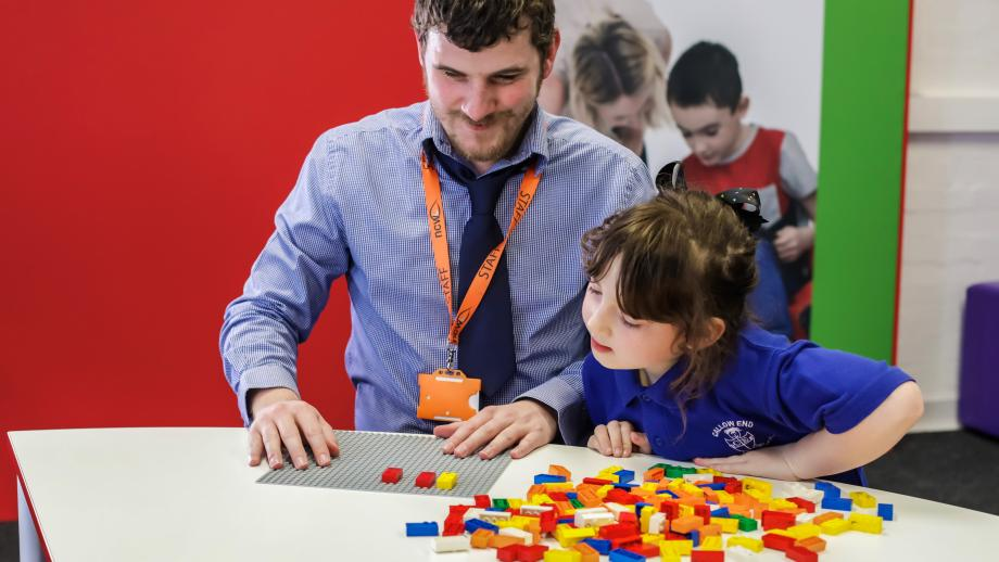 Volwassene en kind spelen met Braille Bricks