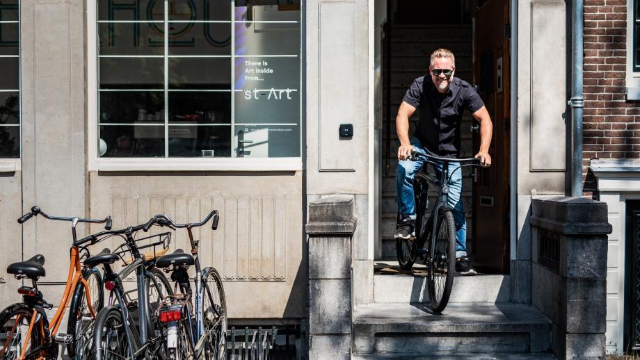 Bert op zijn VanMoof voor de deur Wheelhouse Amsterdam, waar hij kantoor houdt