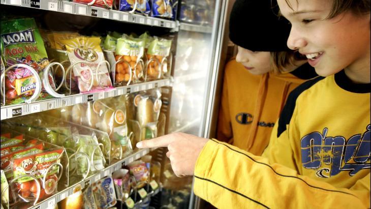 Leerlingen  in Leiden voor een snoepautomaat. Deze heeft ook gezonde versnaperingen.