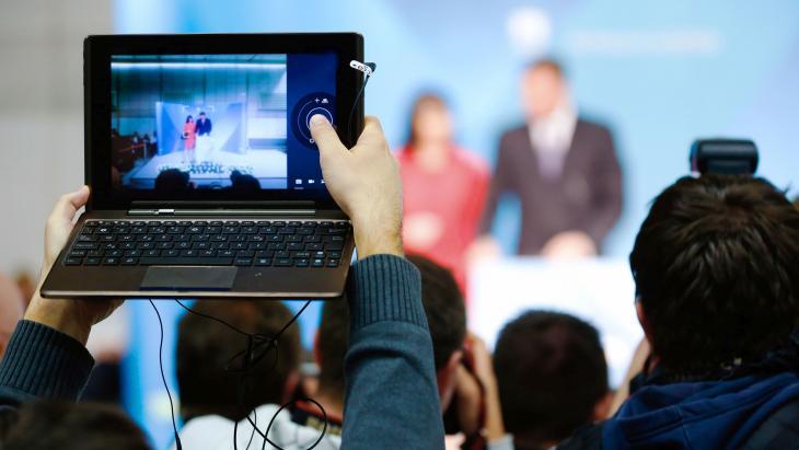 Foto maken met laptop tijdens een persconferentie