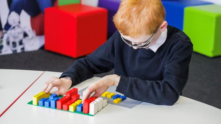 Een kind speelt met de Braille Bricks