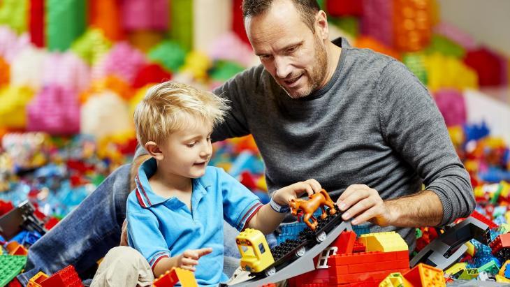 vader en kind spelen met Lego