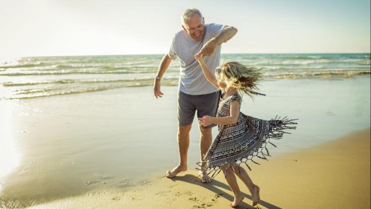 Opa en kleinkind op het strand
