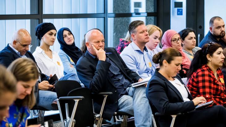 Pieter Klein van RTL Nieuws (met pen) tussen gedupeerde ouders in Tweede Kamer