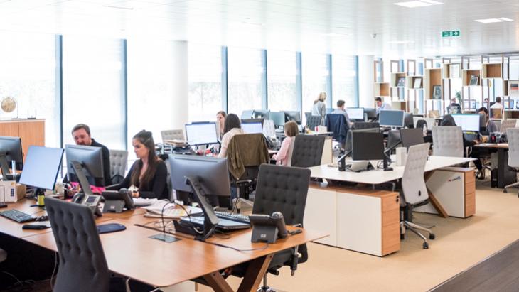 Een kantoor met veel werkende mensen.