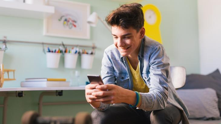jonge jongen kijkt met glimlach naar zijn mobiel terwijl hij op bed zit