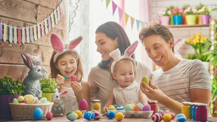 jong gezin viert pasen met geschilderde eieren