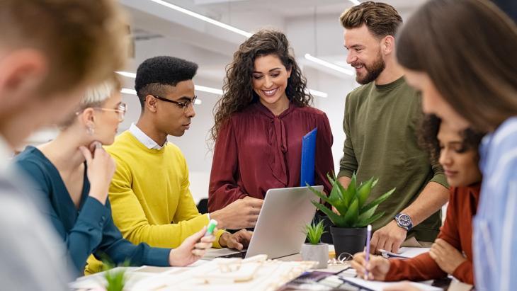 een gemixte groep mensen kijken gecontreerd en tevreden naar een computerscherm