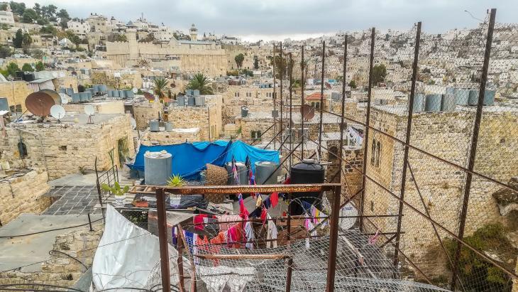 De daken van huizen van Joodse kolonisten en Palestijnse inwoners van de stad Hebron