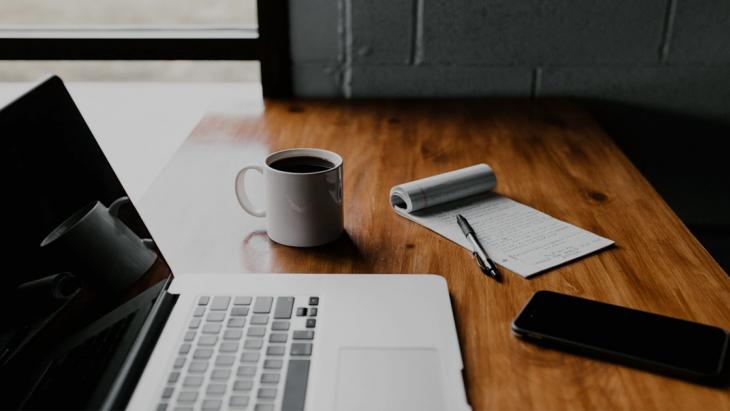 Laptop met papier en koffie